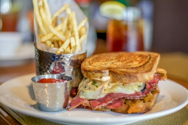 sandwich on plate with ketchup and fries