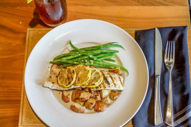 fish dinner plate with lemon garnish, potatoes and green beans