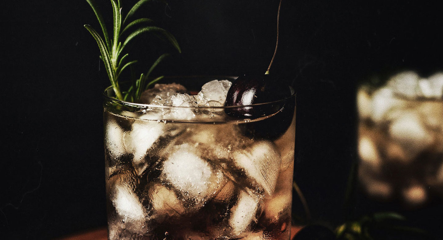 close up of cocktail with garnish in dim lighting