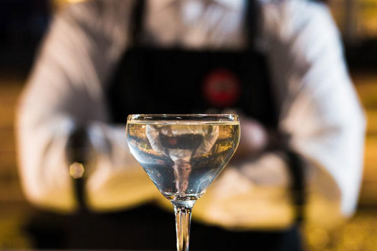 bartender standing behind poured cocktail drink