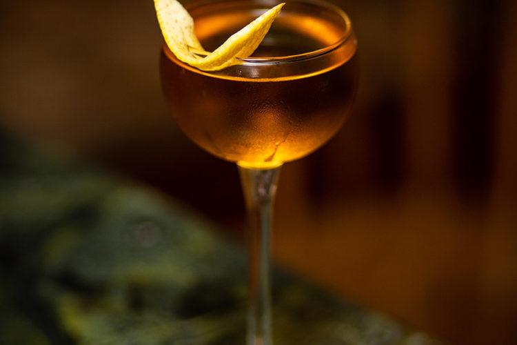 cocktail in long stemmed glass with orange peel garnish