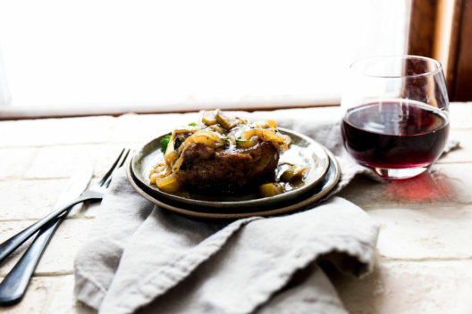 A steak with fried onions and a glass of red wine