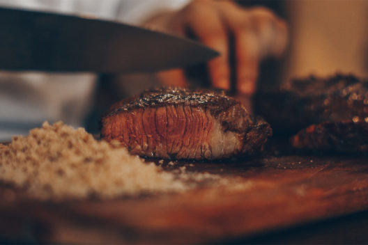 A chef's knife slicing a perfectly cooked steak