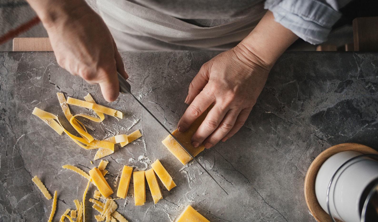 A chef cutting fresh pasta