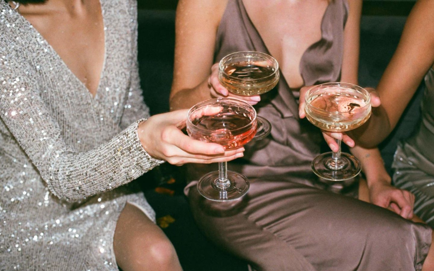 Women in fancy dresses toasting with glasses of wine