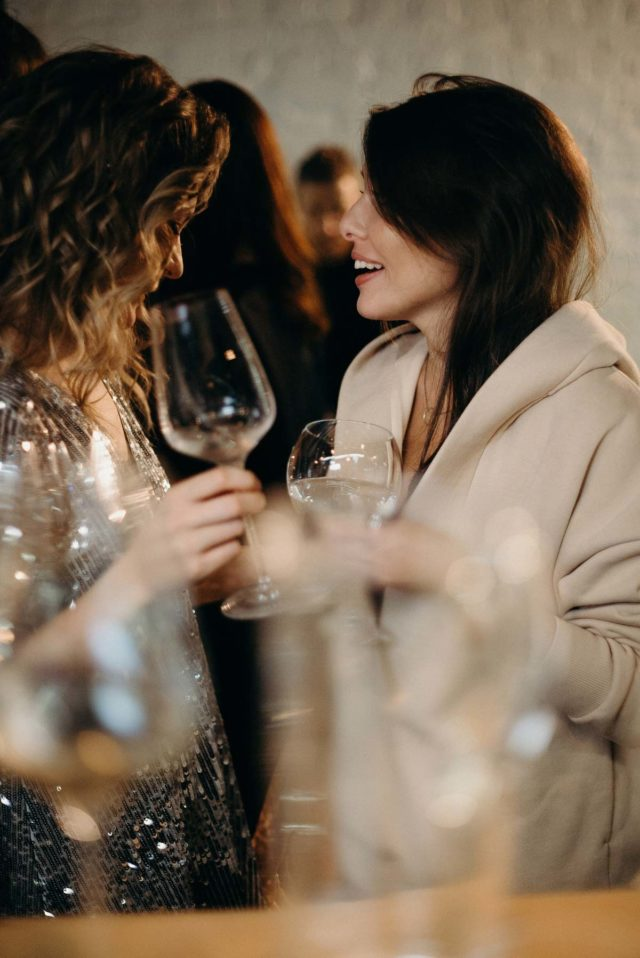 two women holding glasses of wine while chatting