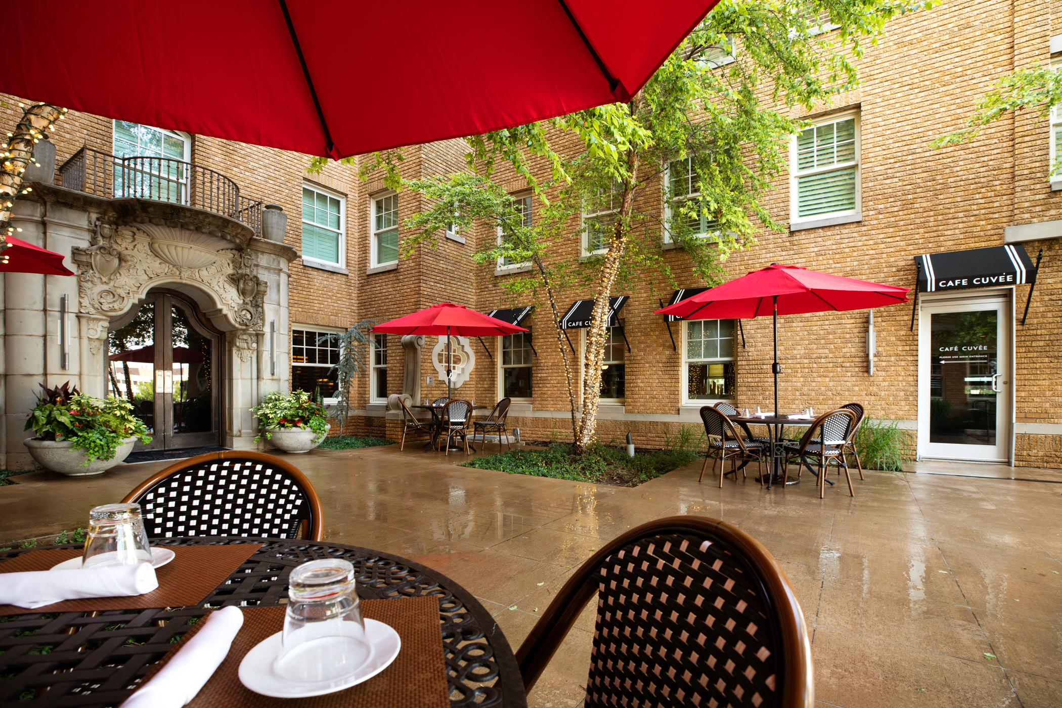 outdoor dining area with brown tables and chairs covered by big red umbrellas