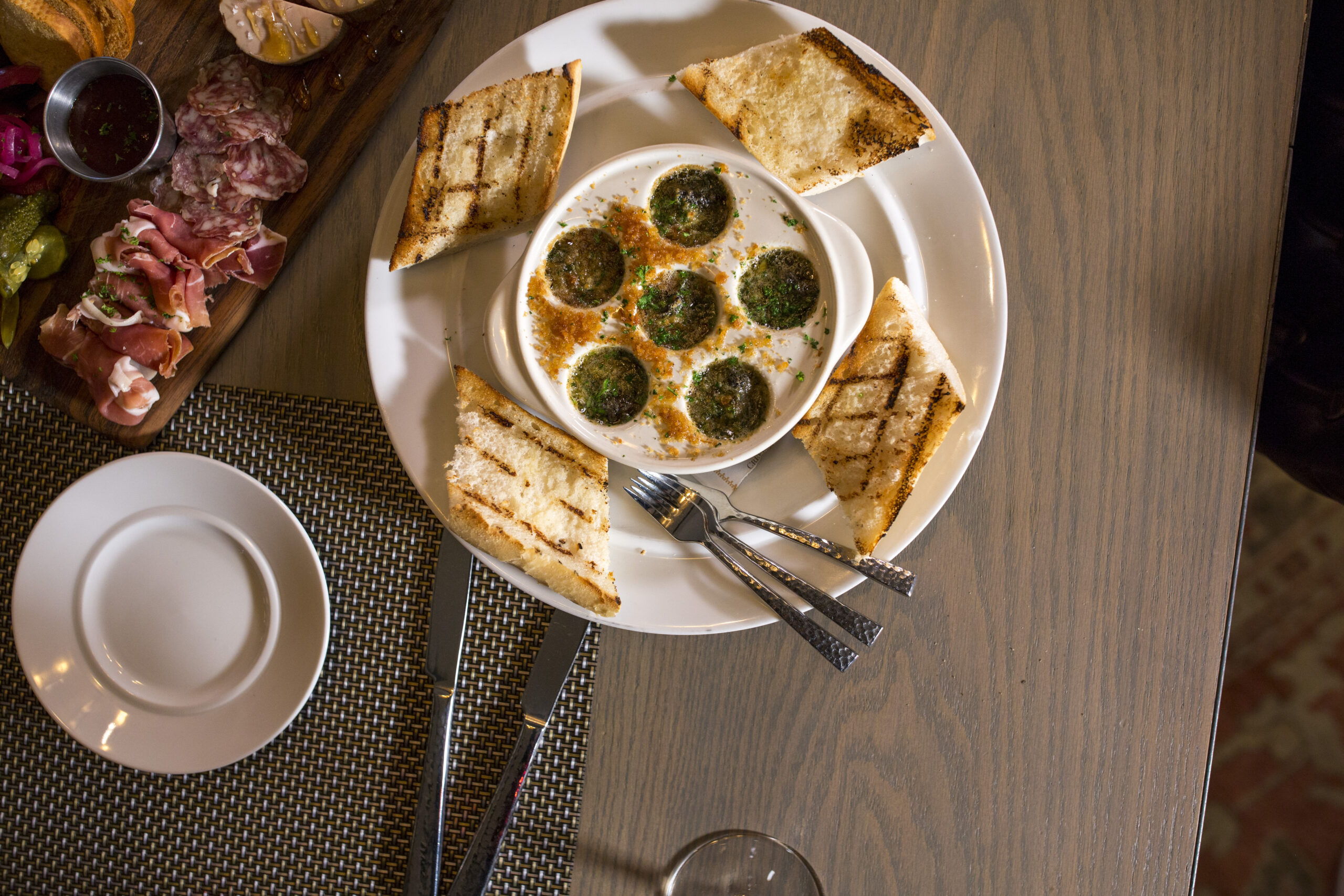 large white plate with bread and escargot on it with a platter of lunch meats next to it