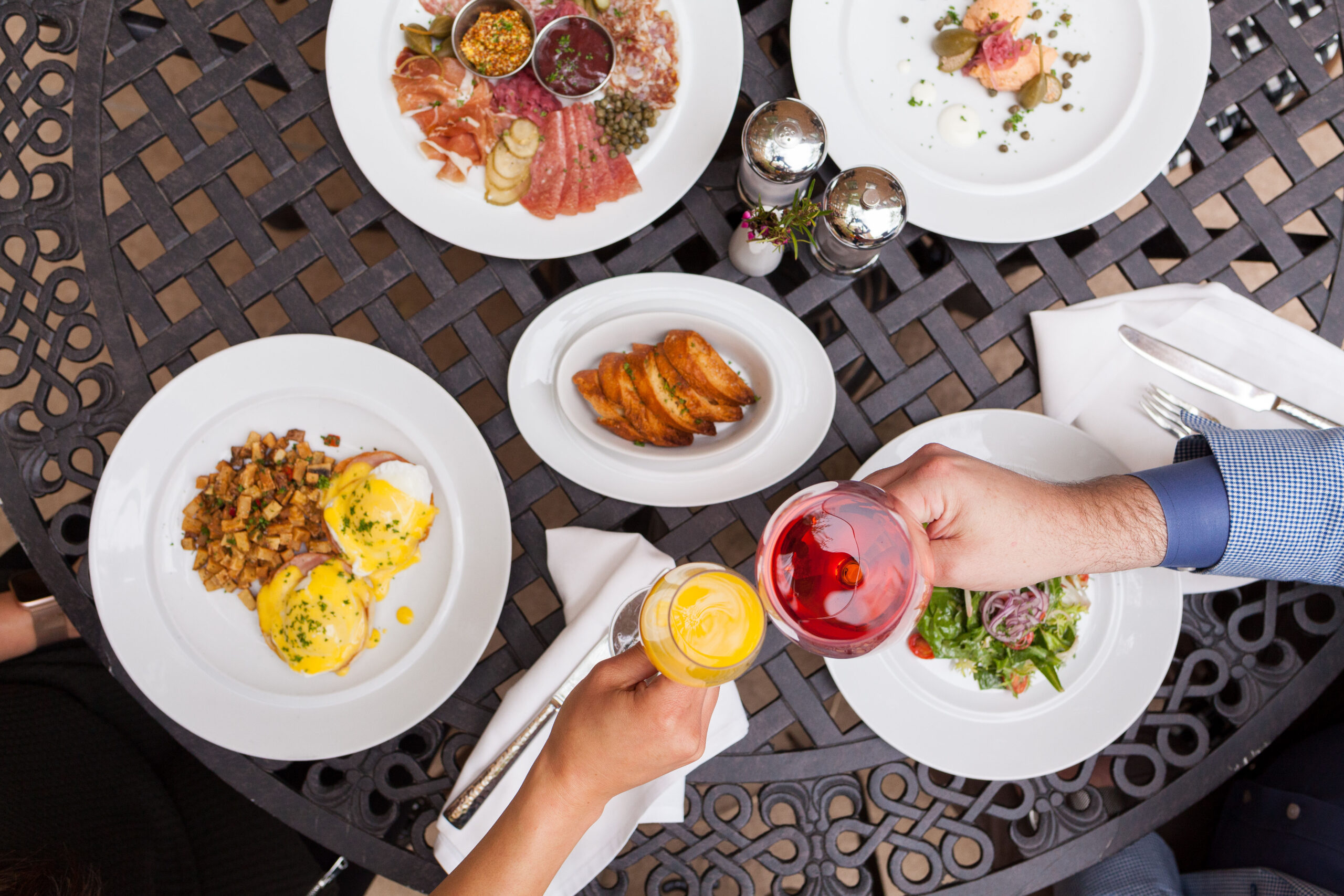 table with four entree dishes and two people clinking their glasses