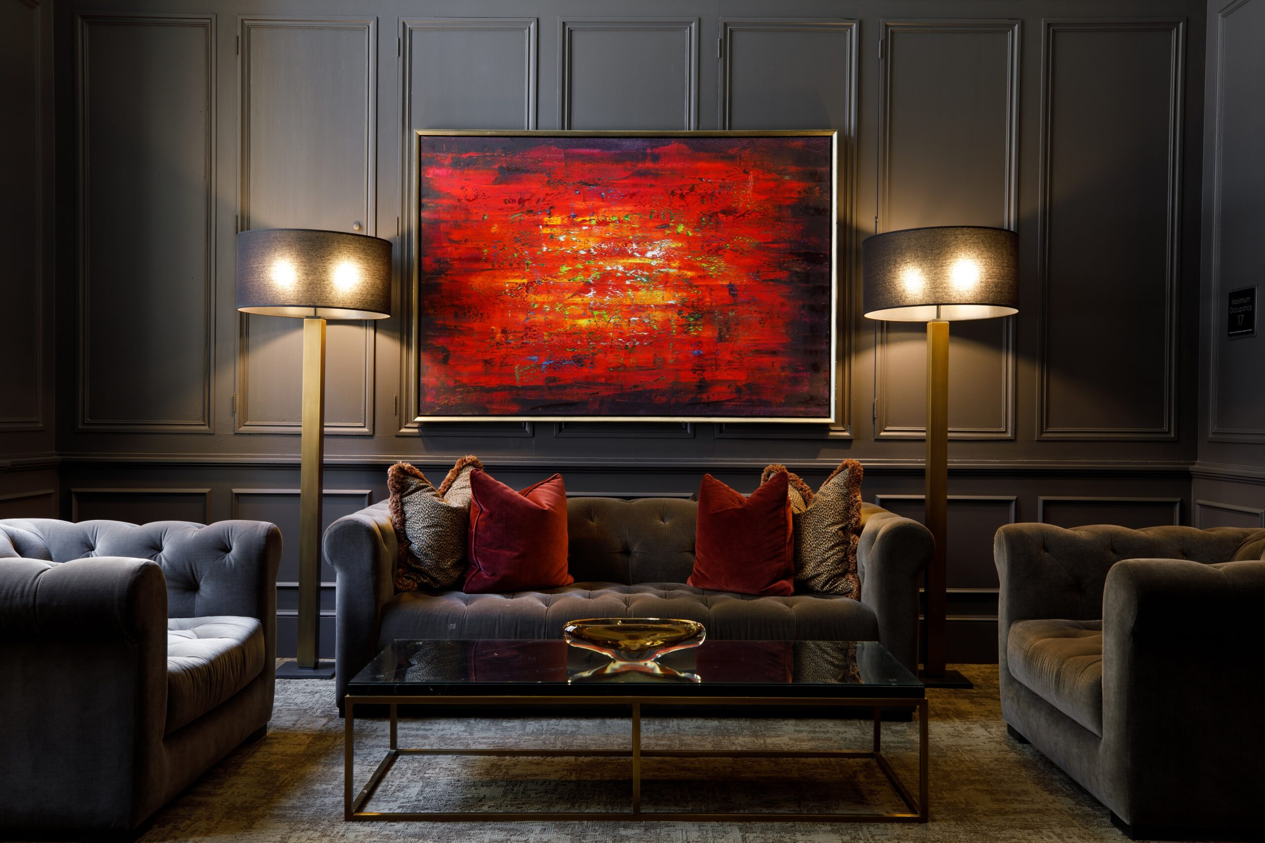 lounge area with dark couches and two large floor lamps