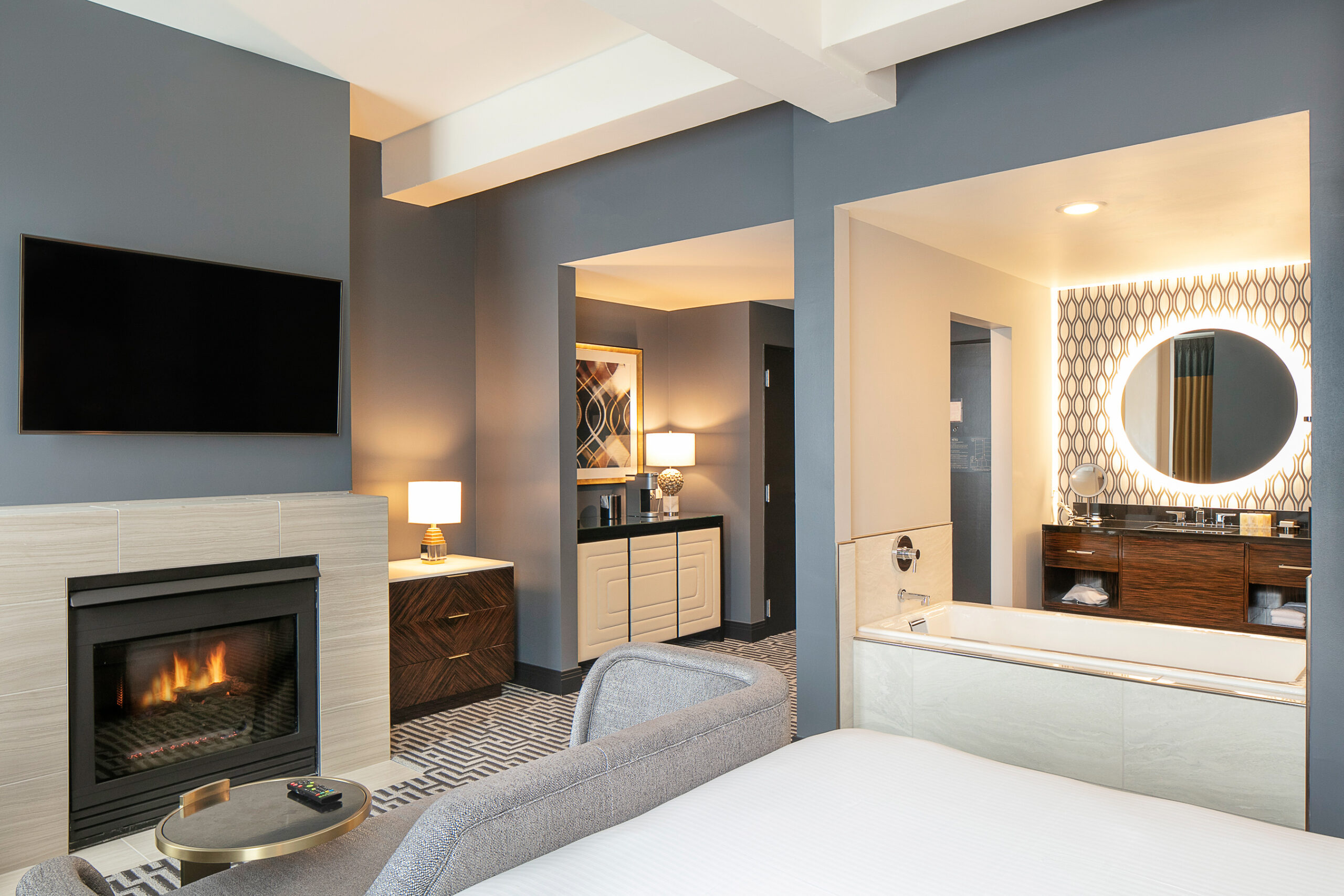 hotel room with blue walls, a small fireplace and a large exposed bathtub and vanity area