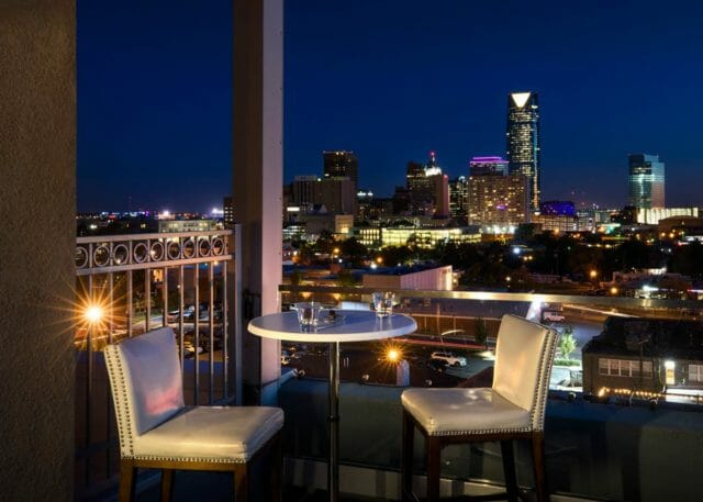 Table for two on balcony of O Bar overlooking Oklahoma City skyline at night