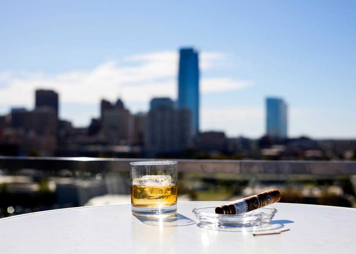 Scotch and cigar on a table overlooking Oklahoma City skyline from O Bar at Ambassador Hotel