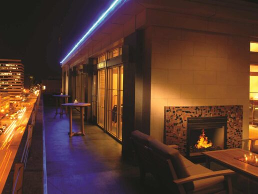 the hotel's outdoor terrace at night with a fireplace