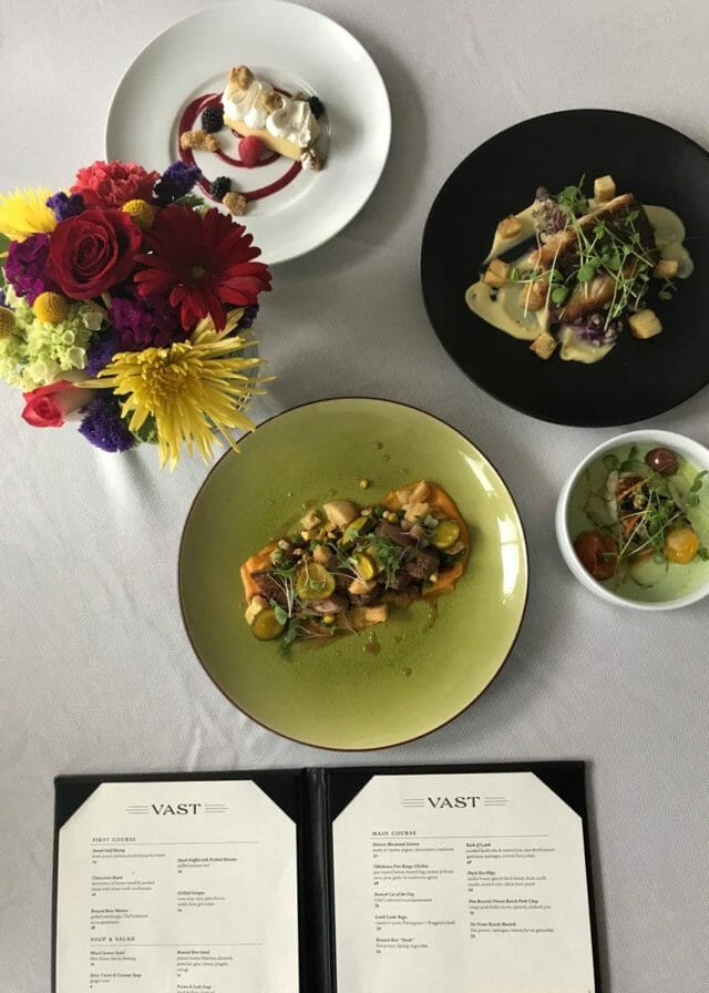 Diverse dishes and a menu on a table at Vast restaurant, Oklahoma City