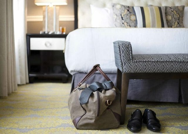 a man's dress shoes and travel bag at the end of the bed