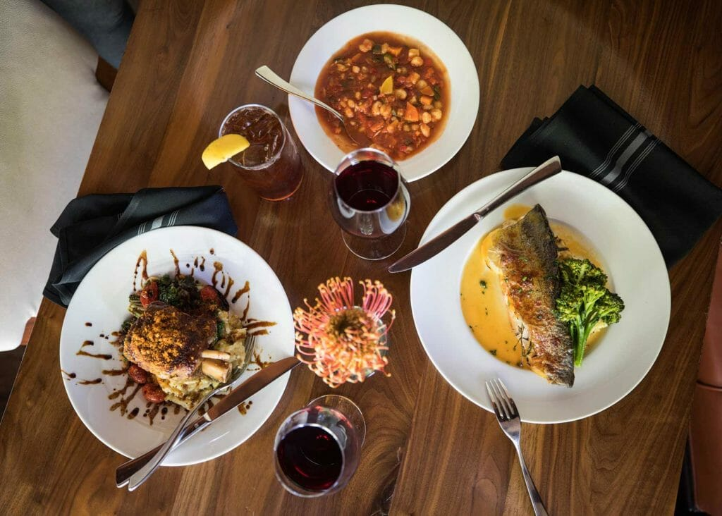 Three dishes and drinks are spread out on a table at Flint in Oklahoma City