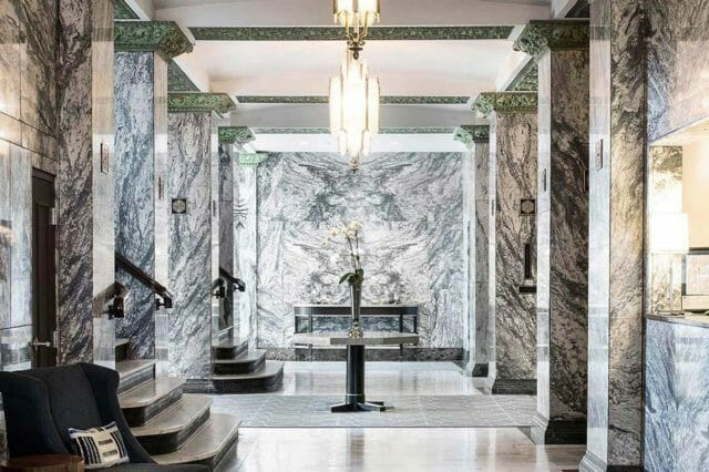 a lavish marble hotel lobby with a bright chandelier