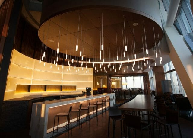 a grand bar interior under many hanging lights with a circular ceiling detail