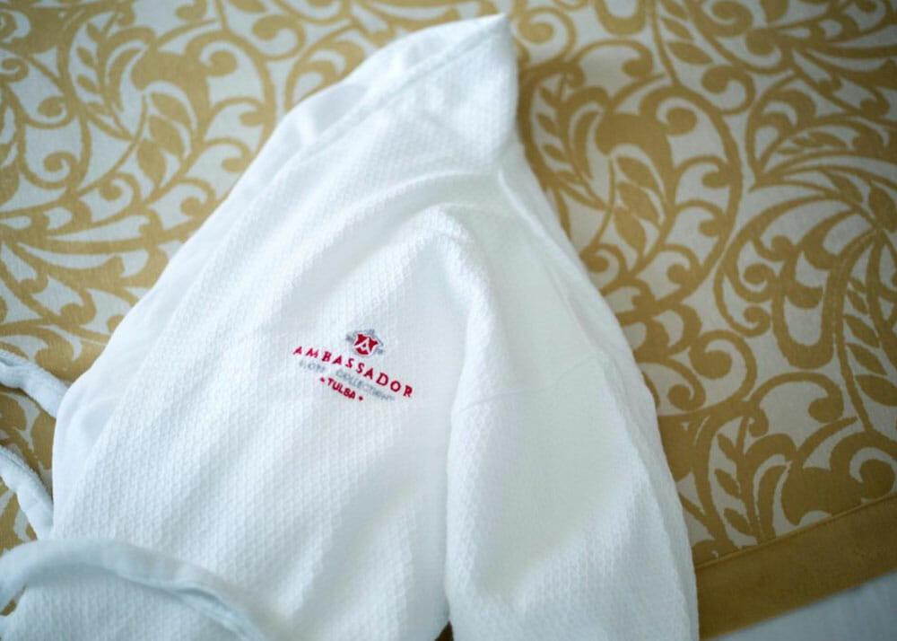 An Ambassador Hotel Tulsa robe lays on a bed