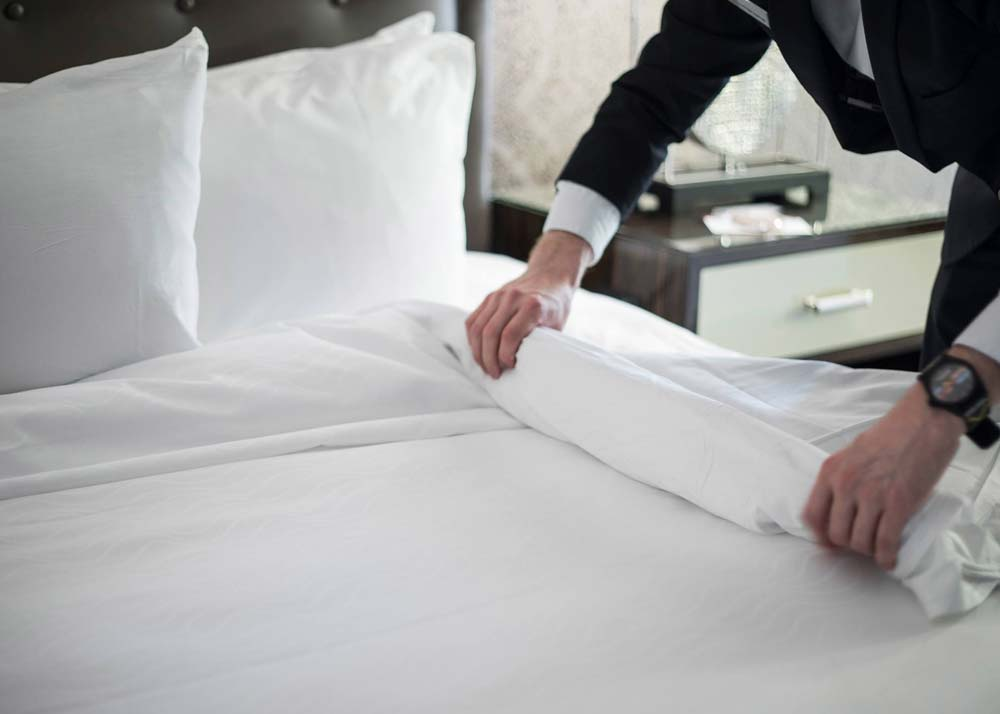 Preparing a hotel bed at Colcord Hotel in Oklahoma City
