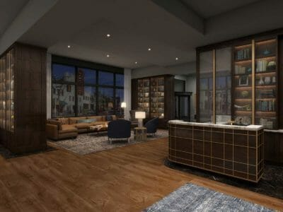 A luxurious hotel lobby with wood floors, dark wood bookshelves, and seating area with sectional sofa and chairs