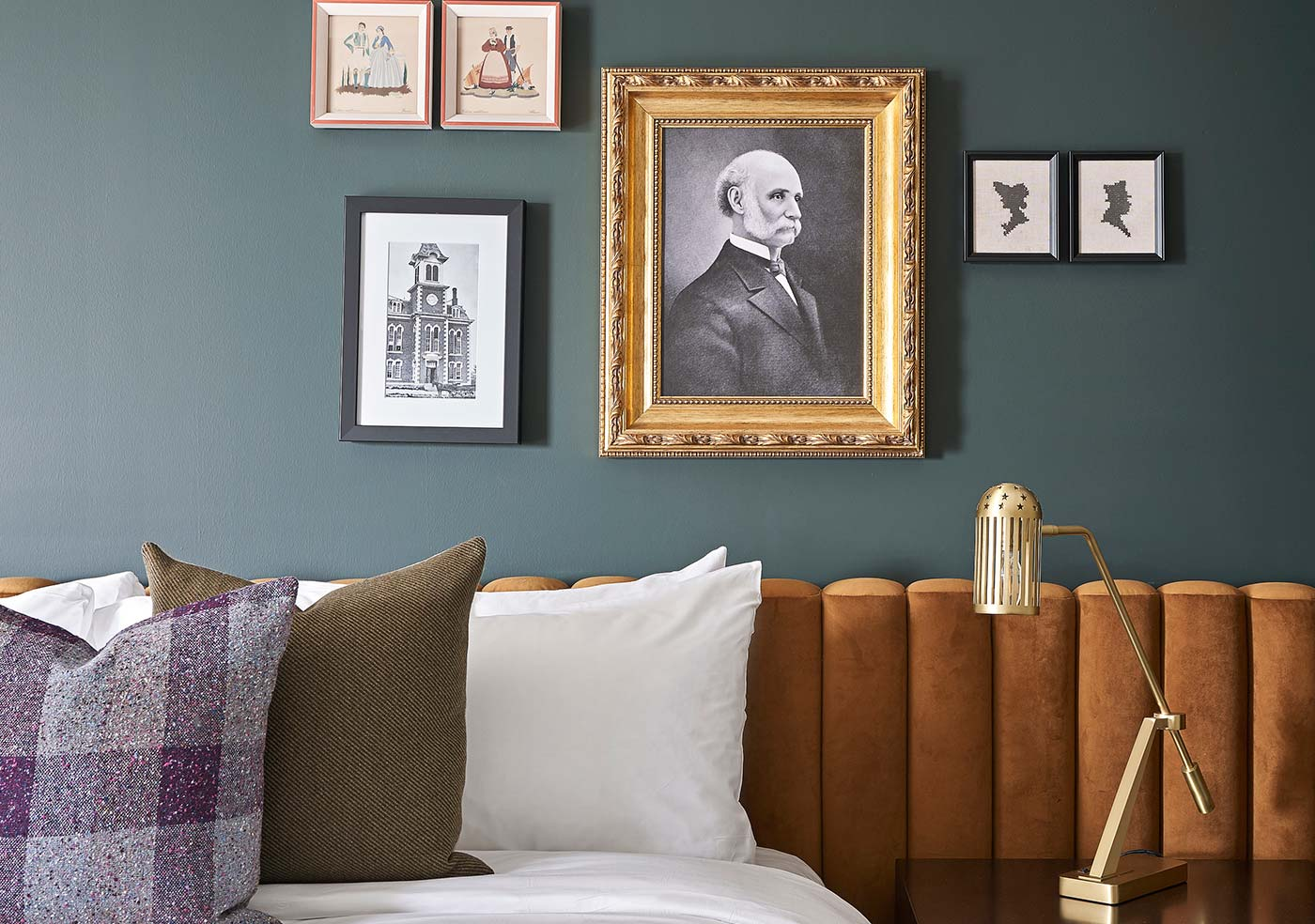close up of hotel guest room bed with decorative pillows and artwork on wall
