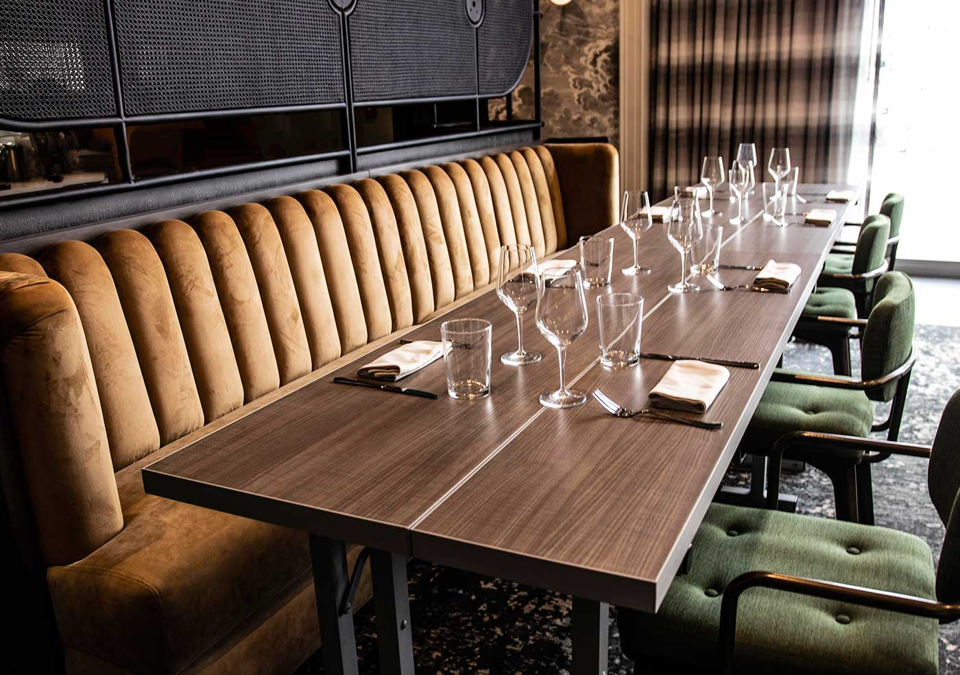 large dining table with a brown suede booth with green chairs