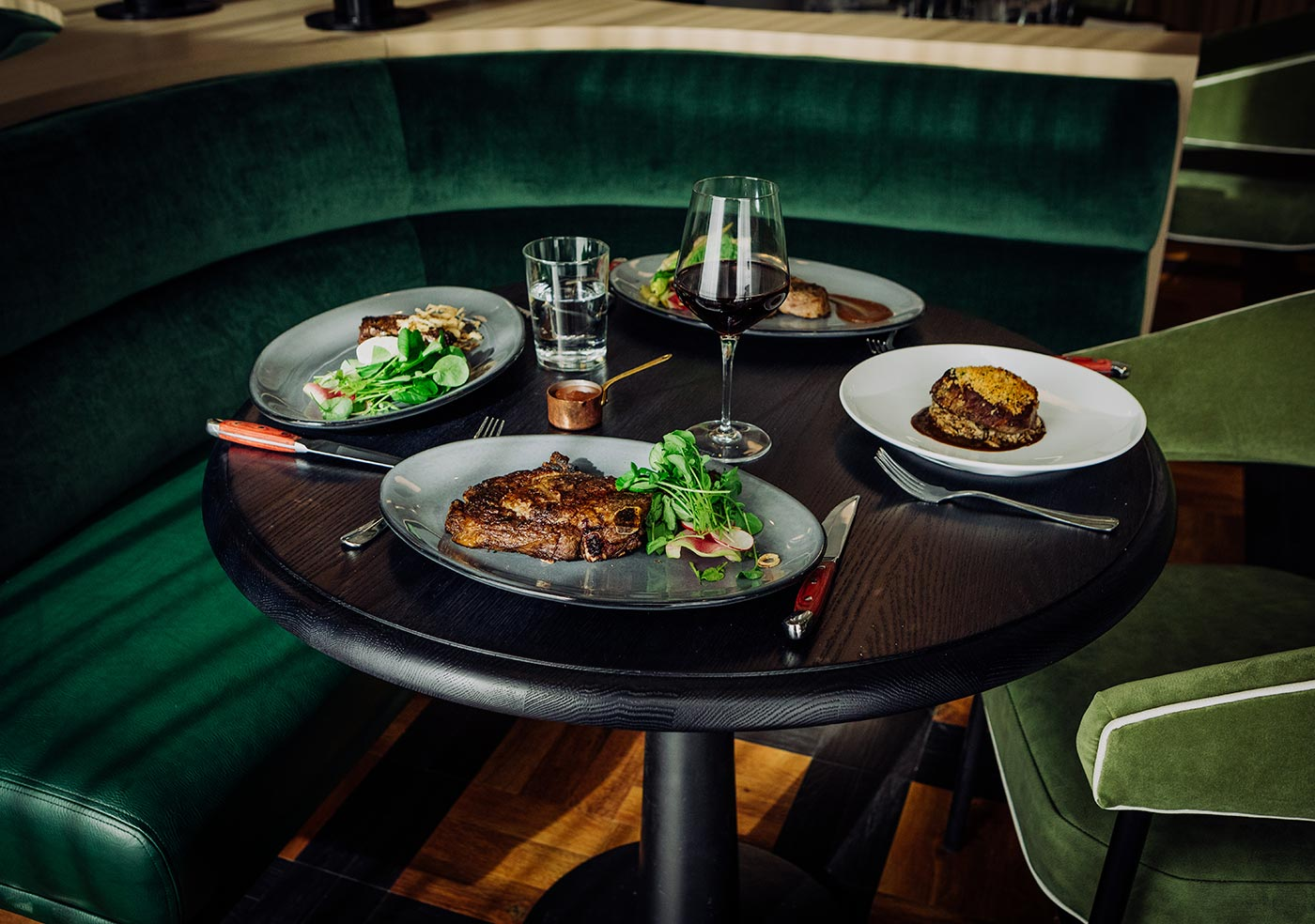 round table with a green suede booth and a green suede chair