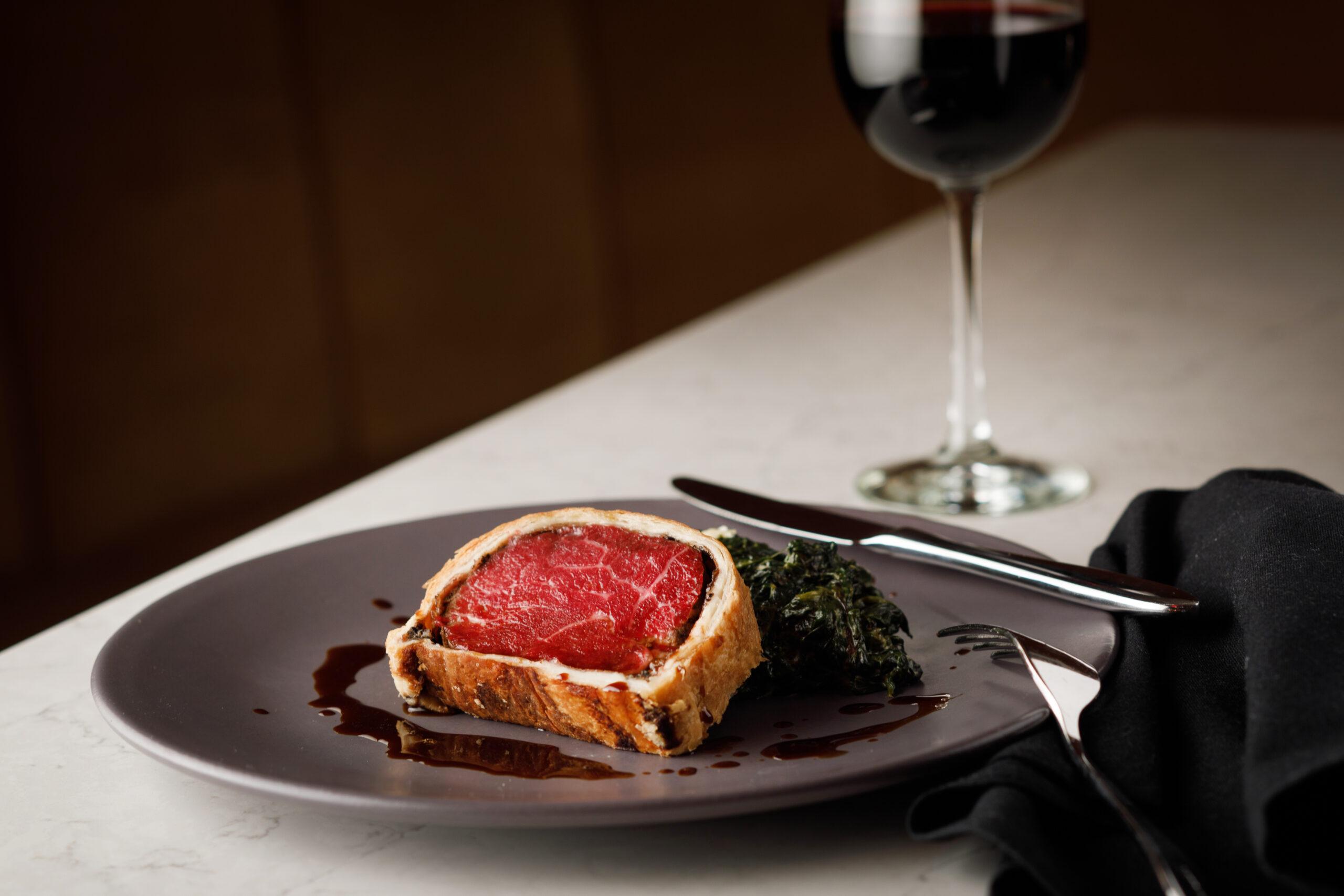 beef wellington on a grey plate beside a wine glass
