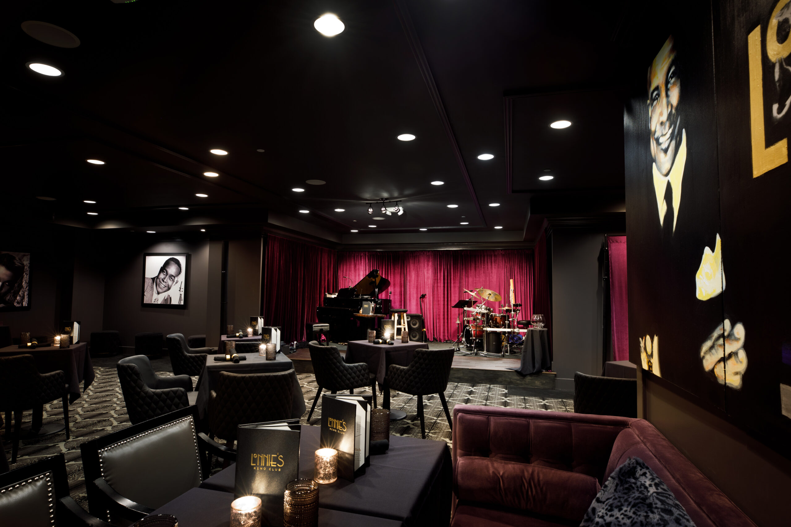 dark club lounge with a stage that has a piano and drumset on it
