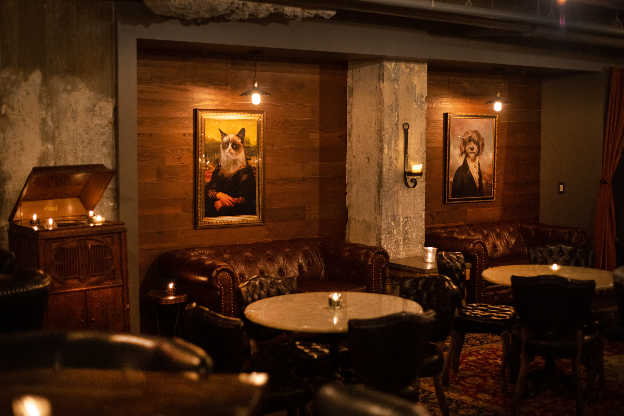 dark lounge area with big leather couches and small white round tables with animal artwork on the walls