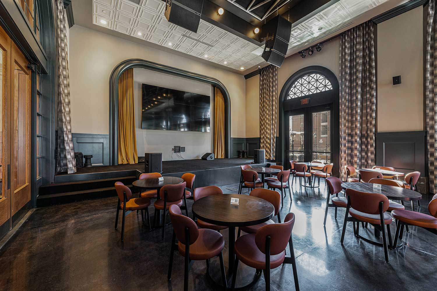The Third Rail event space with dining tables and chairs and stage