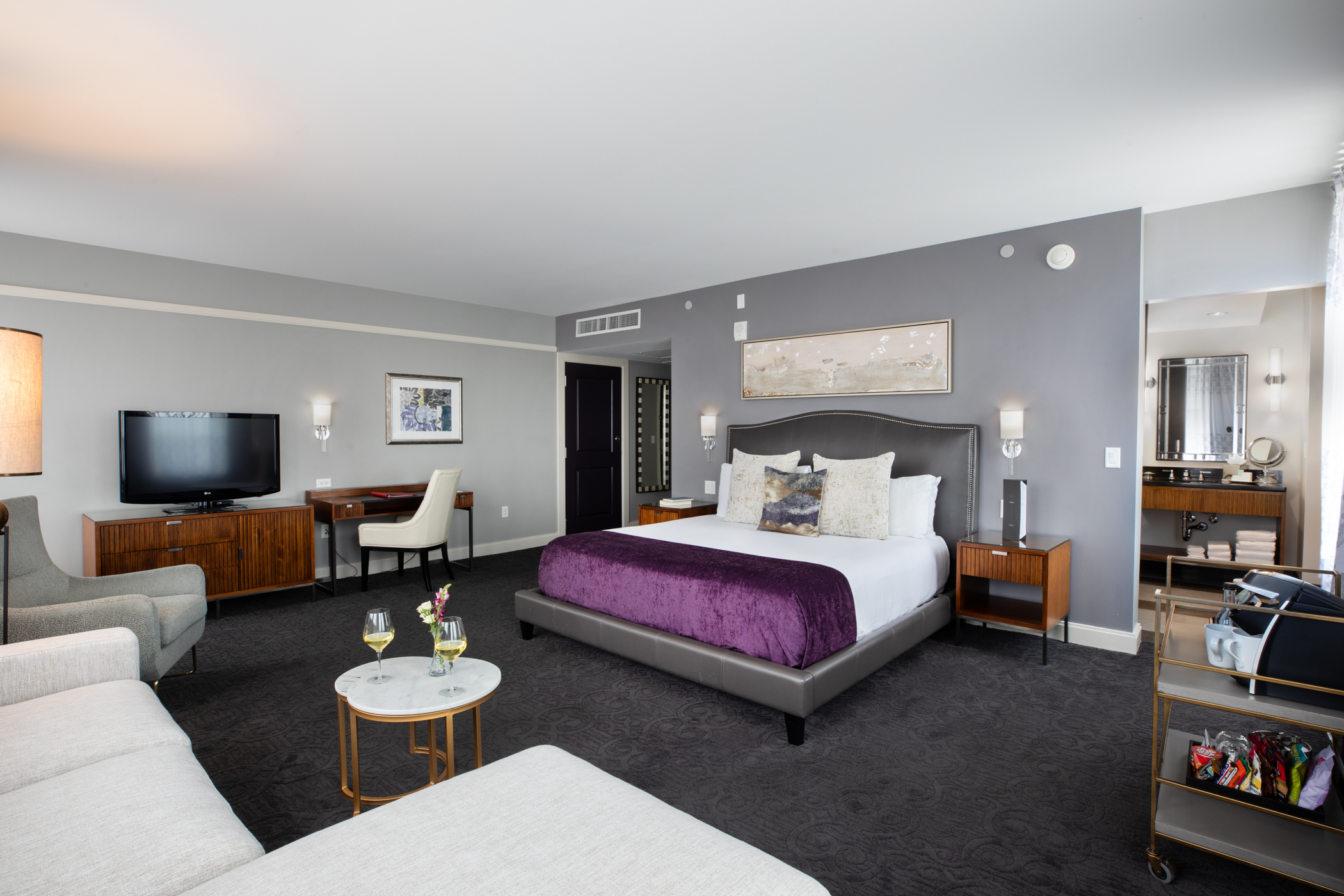 hotel room with grey walls and couches and a large bed with purple linens