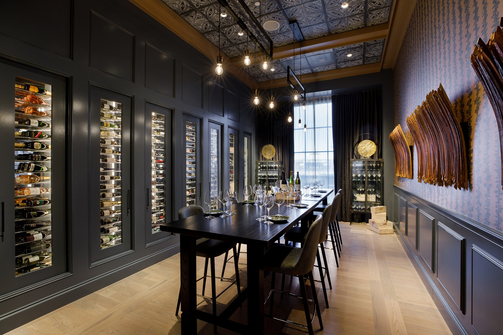 long dining table in a room with a wall displaying hundreds of wine bottles