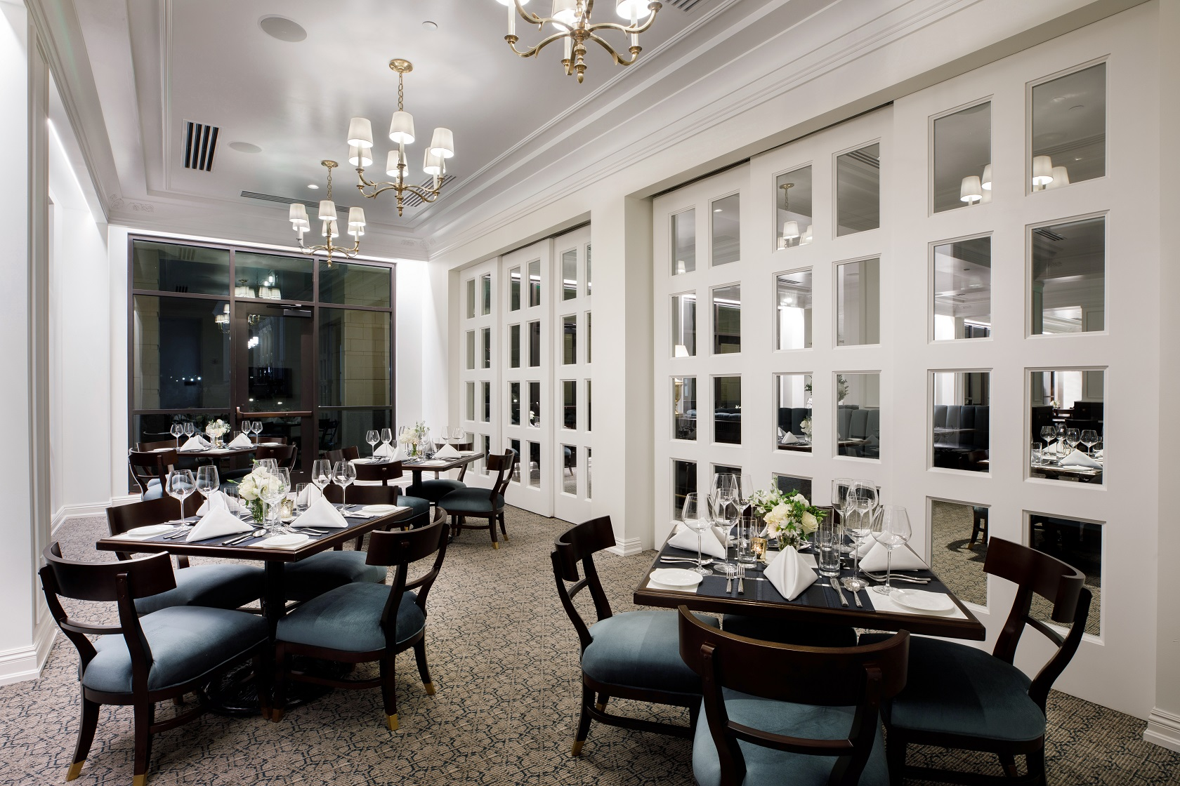large white room with light fixtures on the ceiling and dark tables and chairs