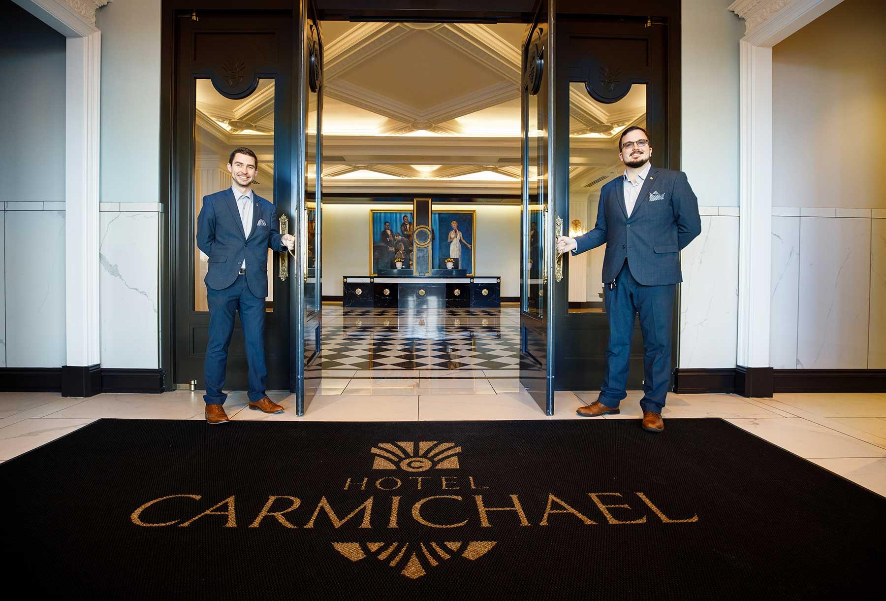 two men holding doors of hotel carmichael open