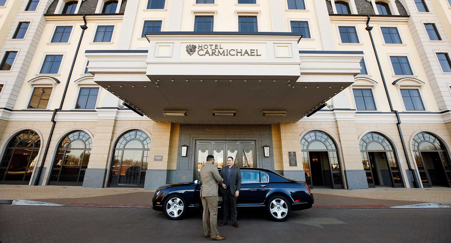 two men shaking hands outside of car in front of hotel carmichael