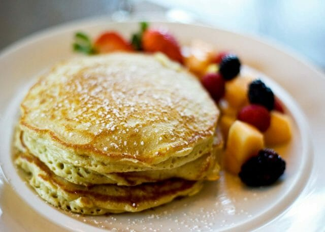 three plump pancakes next to fresh fruit