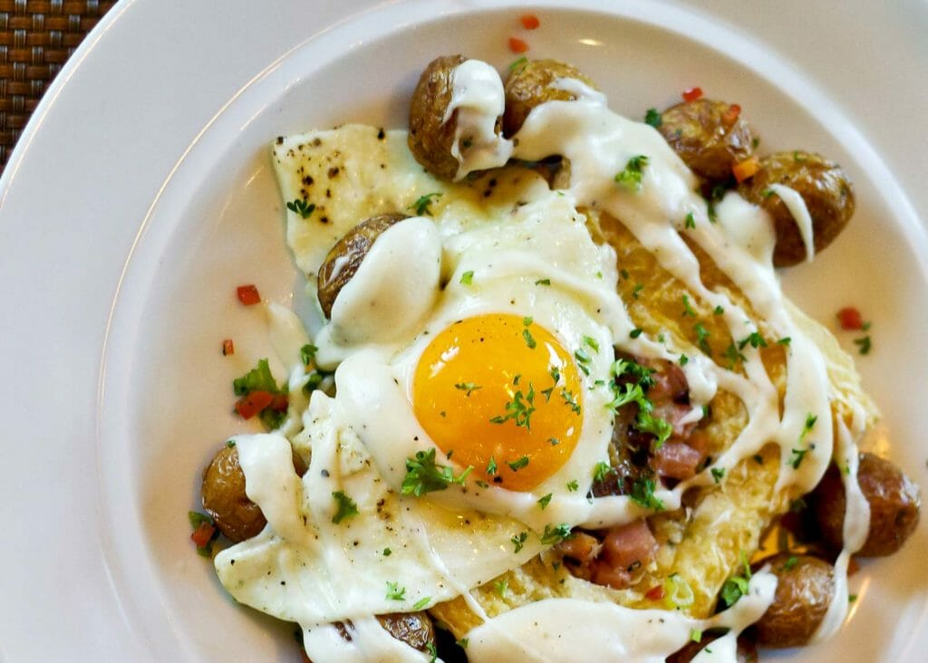 a breakfast egg on top of potatoes