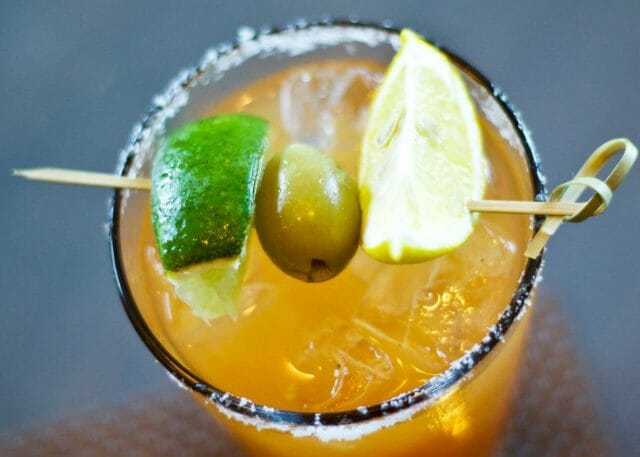 a bright cocktail with olive and limes