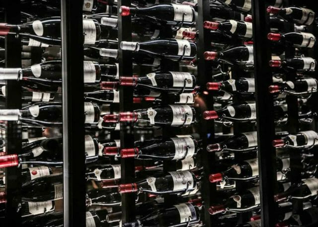 a wine rack with rows of red wine bottles