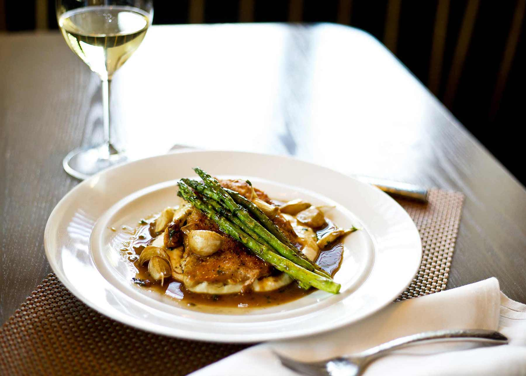 a dinner plate of chicken, potatoes and asparagus with a glass of white wine