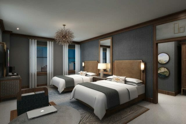 two queen beds in a luxury hotel room with light grey carpet, dark grey walls, and dark wood moulding and framing