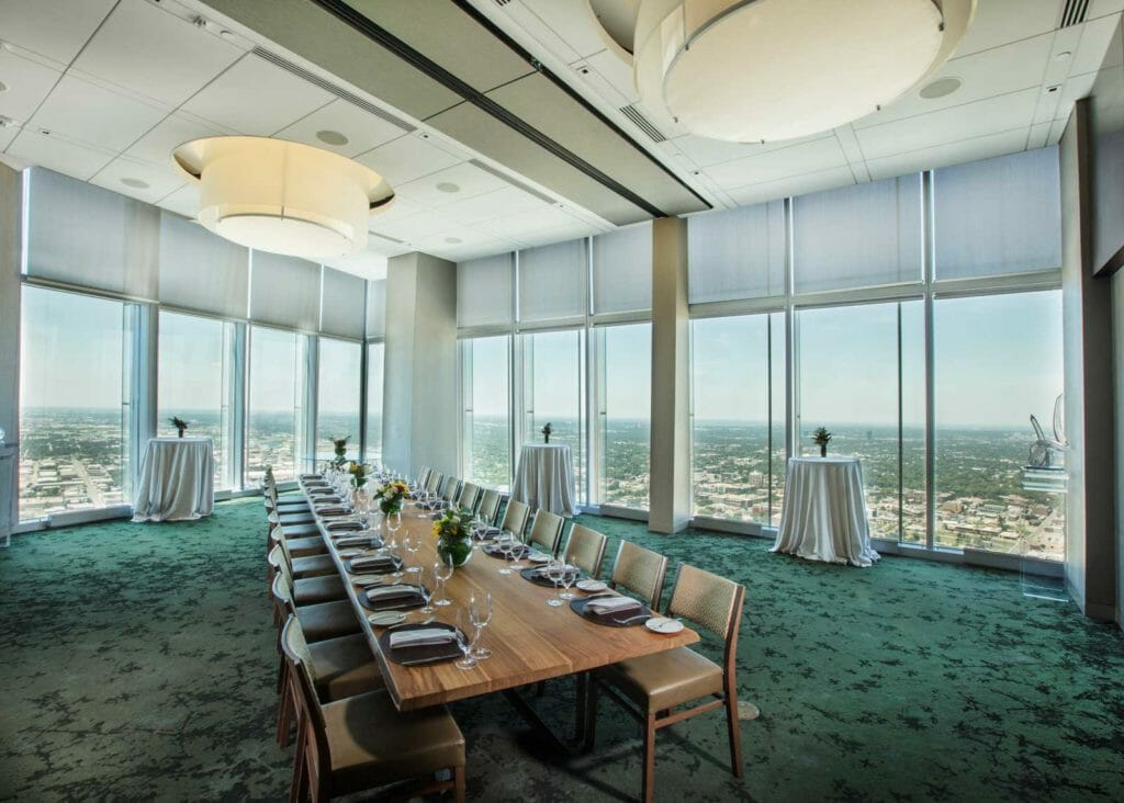 a long dining table with twelve seats on either side prepared with place settings within an event space with floor to ceiling windows overlooking the city skyline