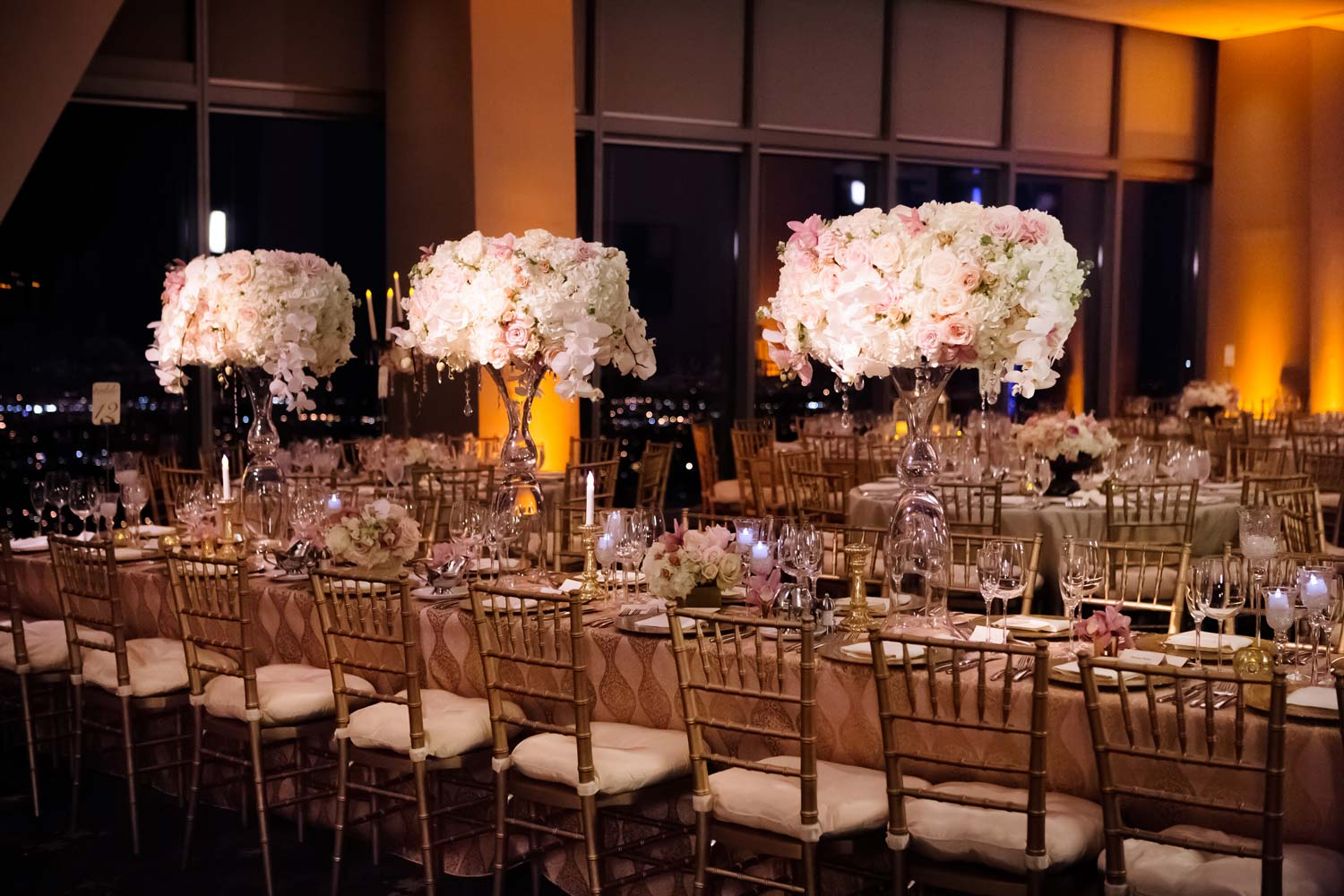 a dimly lit wedding venue with beautiful long tables and large flower centrepieces