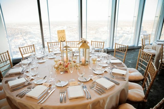 a round dining table set for a wedding dinner with plate settings, centre pieces next to the floor to ceiling windows