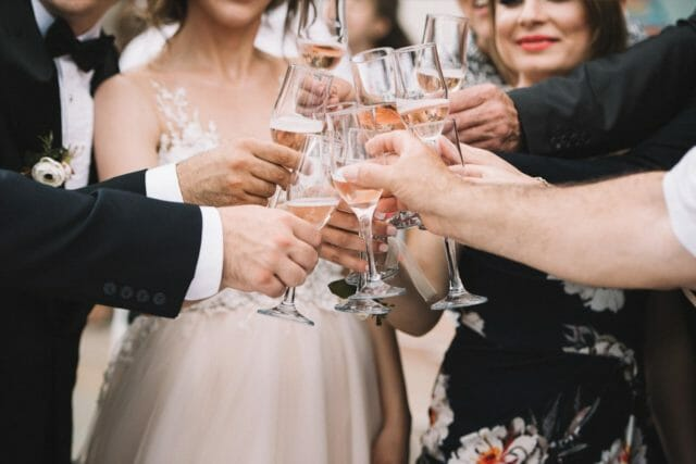 a group of friends cheersing glasses during a wedding celebration