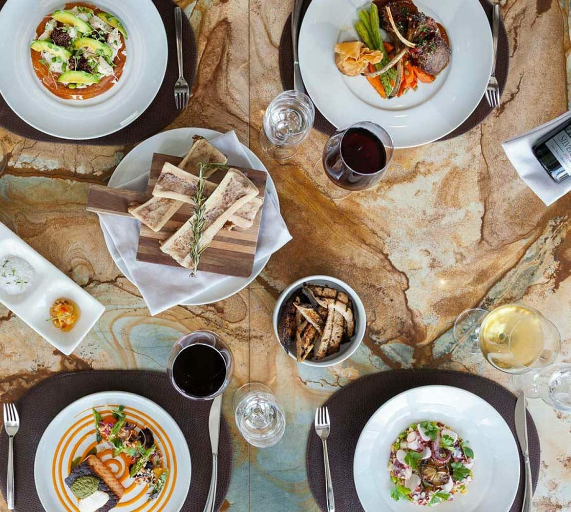 bird's eye view of a table at Vast filled with plates full of freshly cooked food and prepared drinks