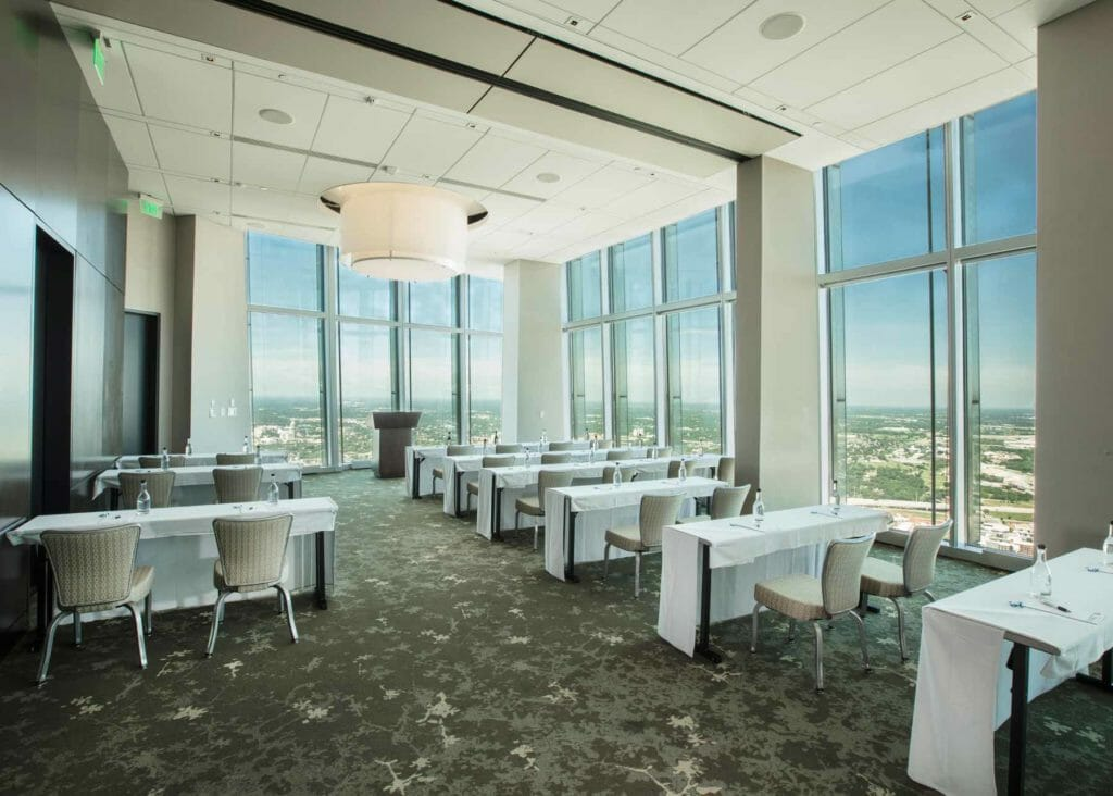 a grand meeting or event venue at Vast that is brightly lit by the large floor to ceiling windows overlooking the city skyline